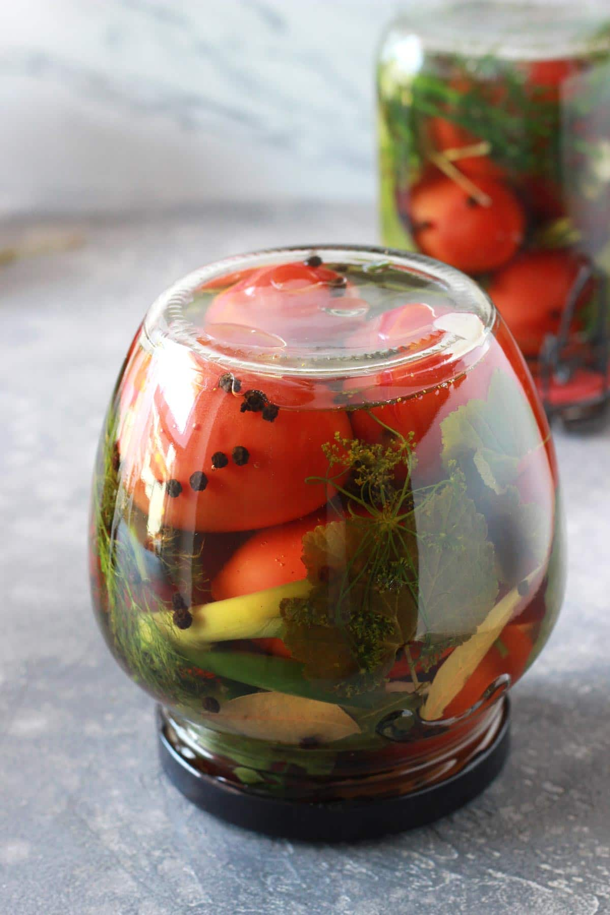 A jar with tomatoes upside down.