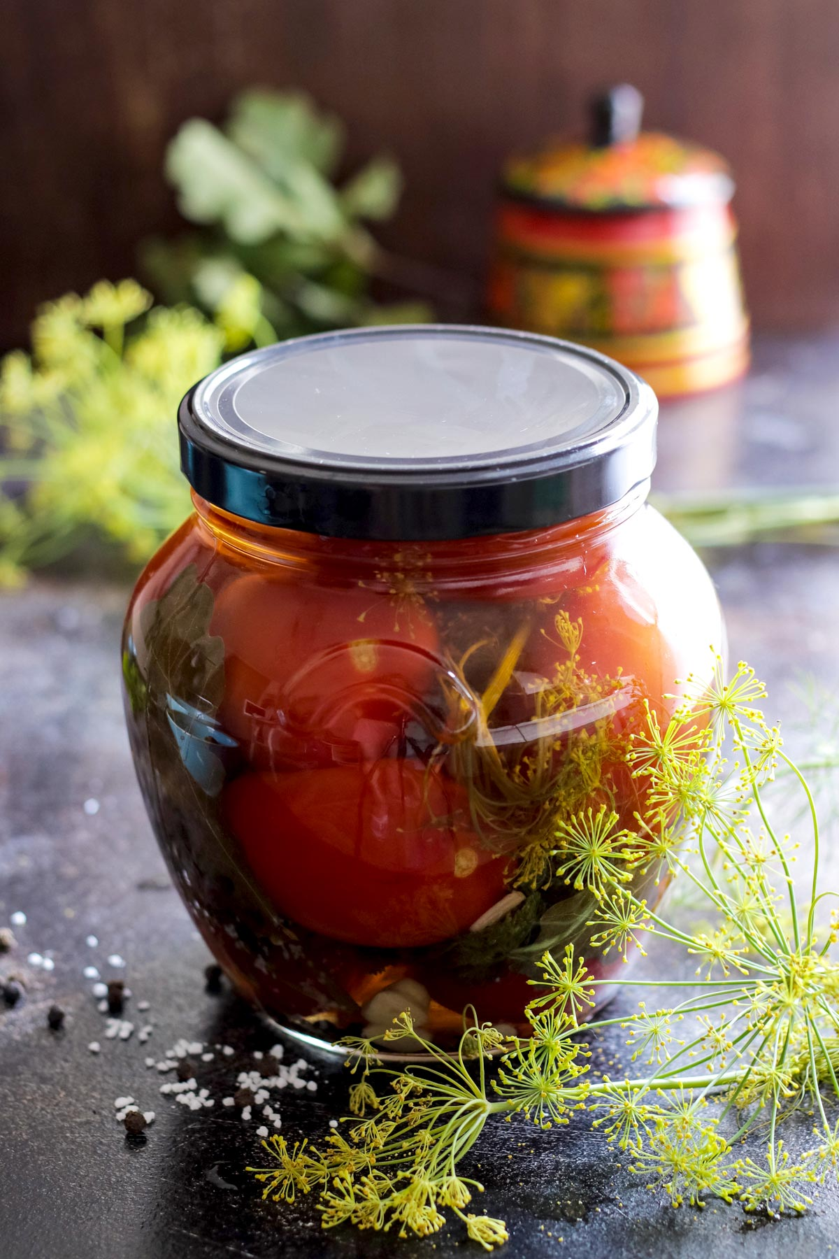 Closed jar with pickled tomatoes with dill umbrellas