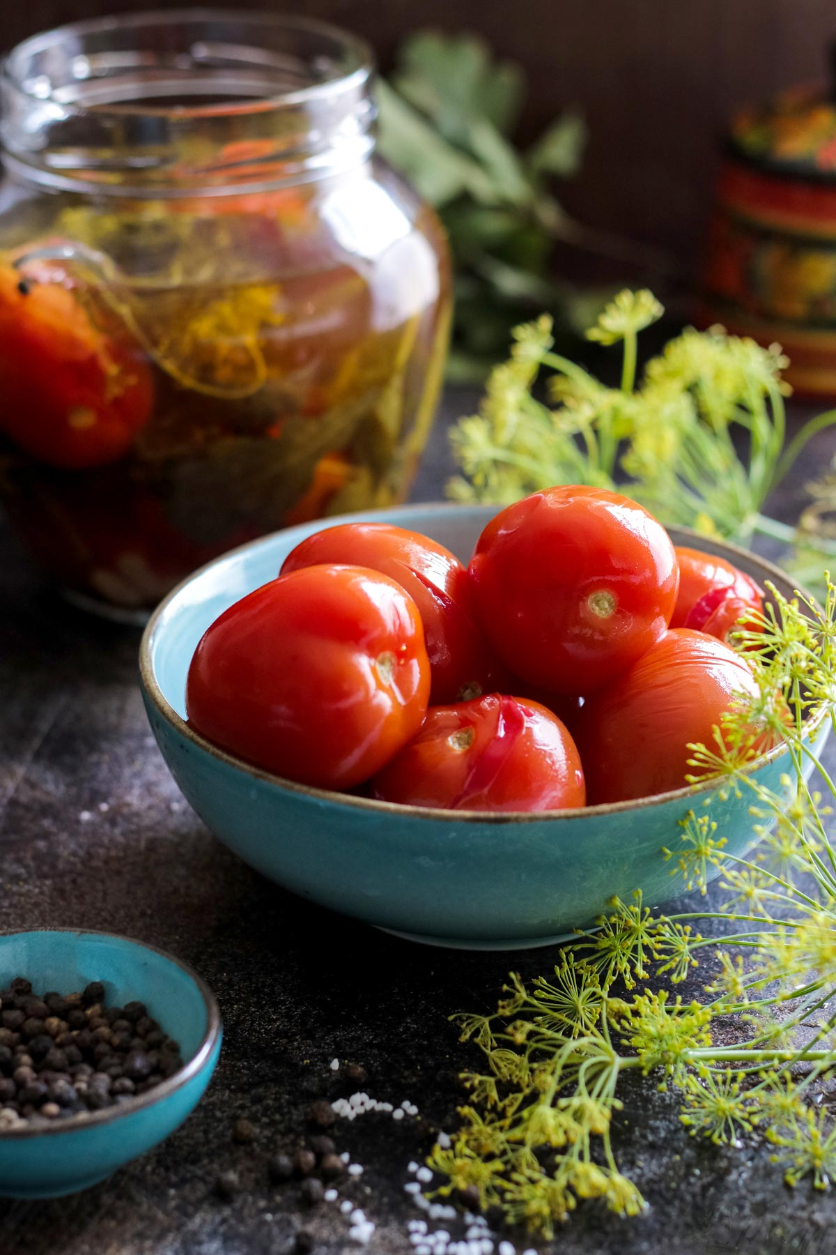 Pickled tomatoes in a bowl next to a jar.