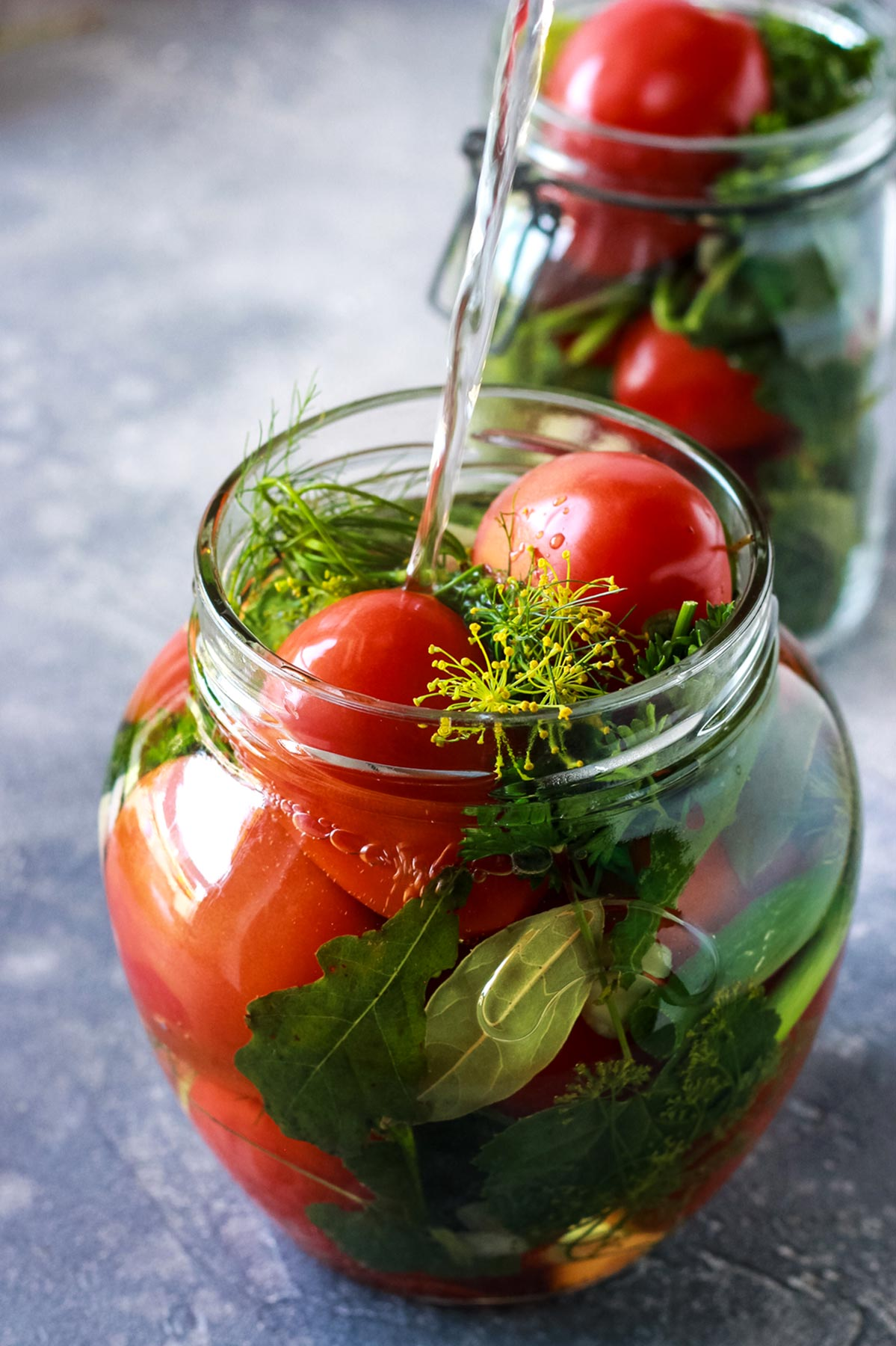 Pouring boiling water into a jar with tomatoes.