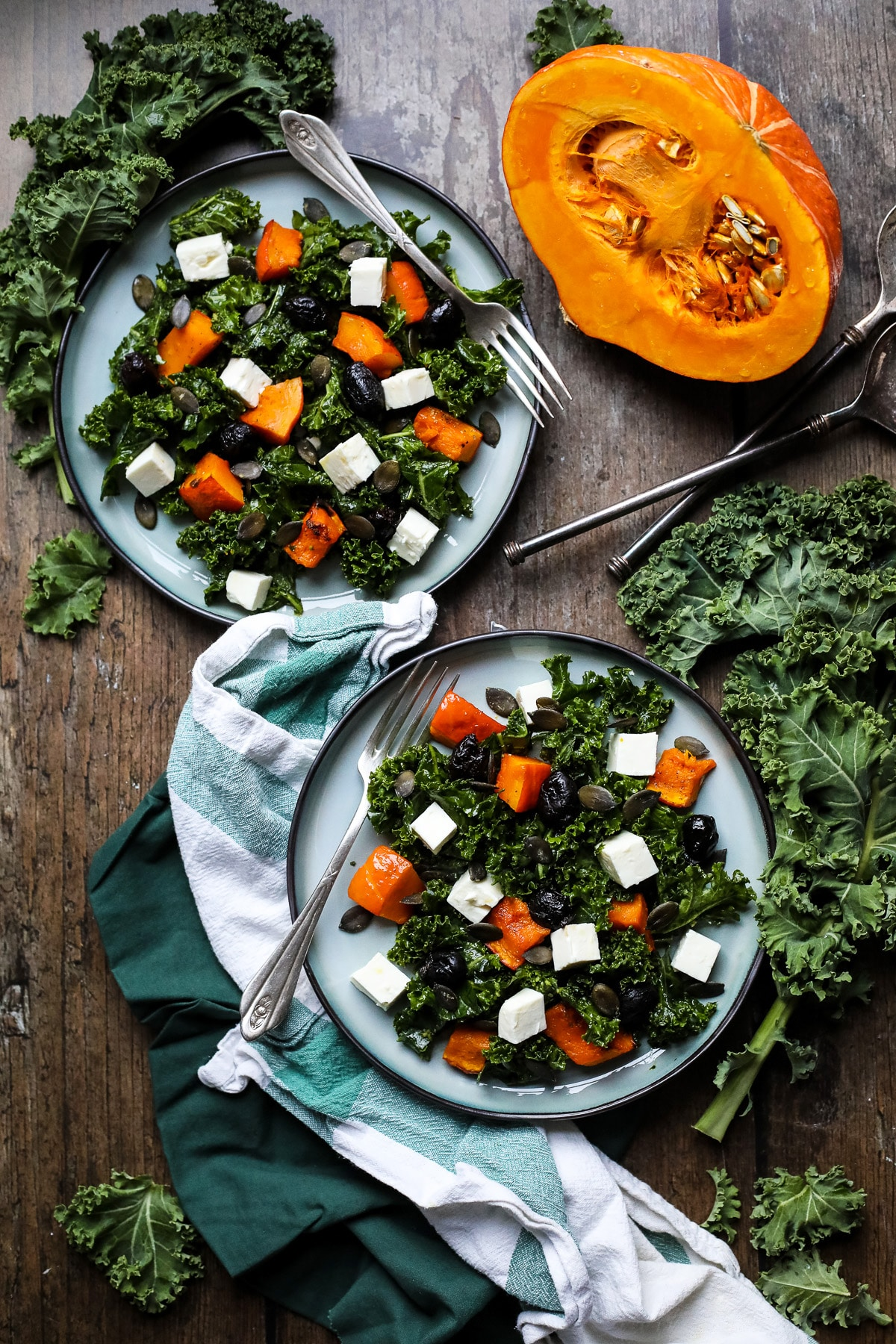 Plates with kale salad with pumpkin and feta.