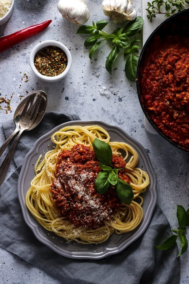 Vegan Spaghetti Bolognese on a Plate Next to Sauce