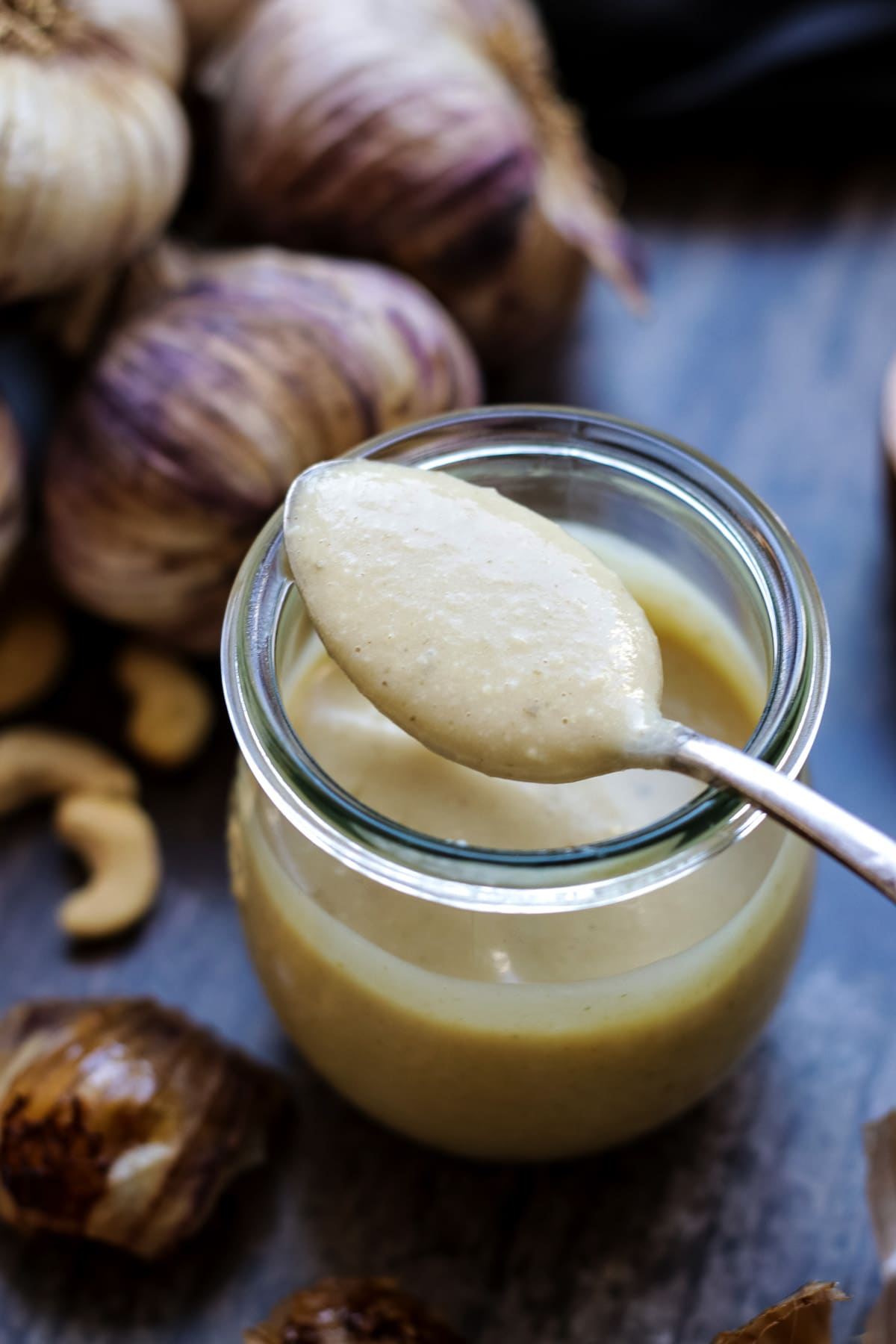 A jar of roasted garlic sauce with a spoon.