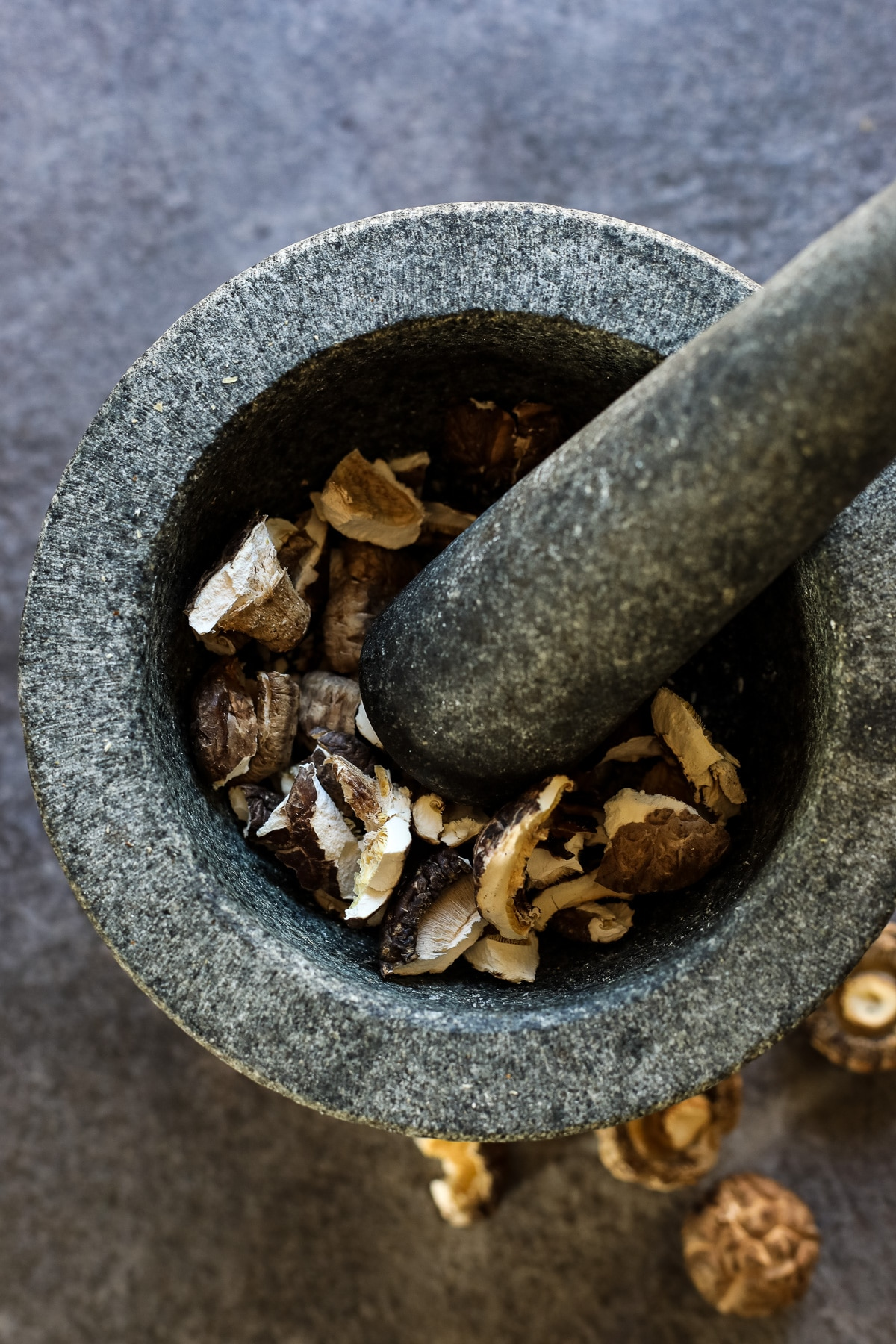 Breaking Dried Shiitake Mushrooms with a Mortar and Pestle.