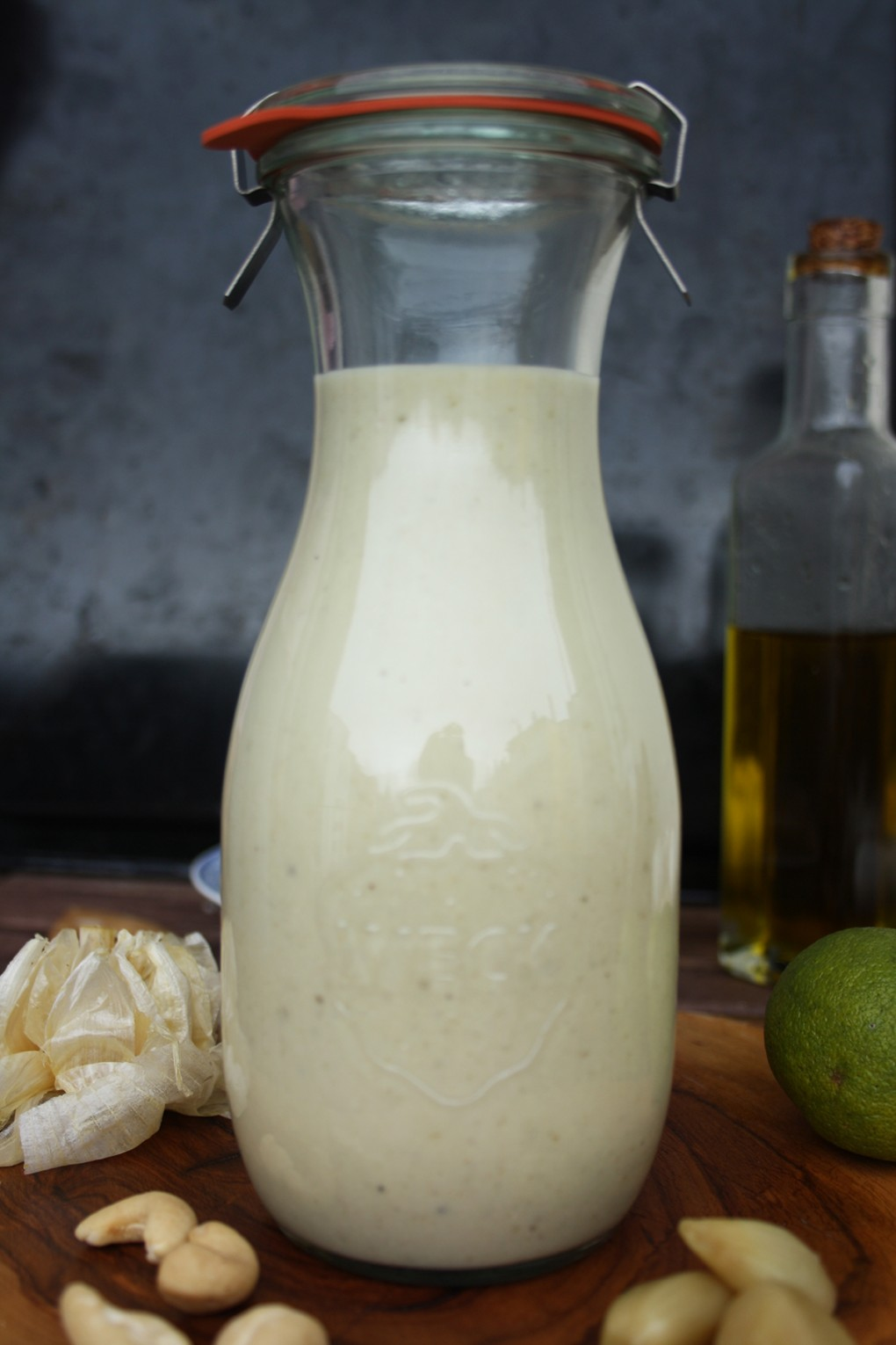 Roasted Garlic Dressing in a Bottle Ready for Serving with Garlic Cloves on the Table