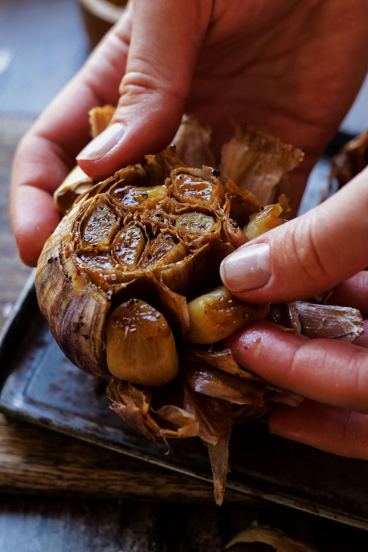 Peeling roasted garlic by hand.