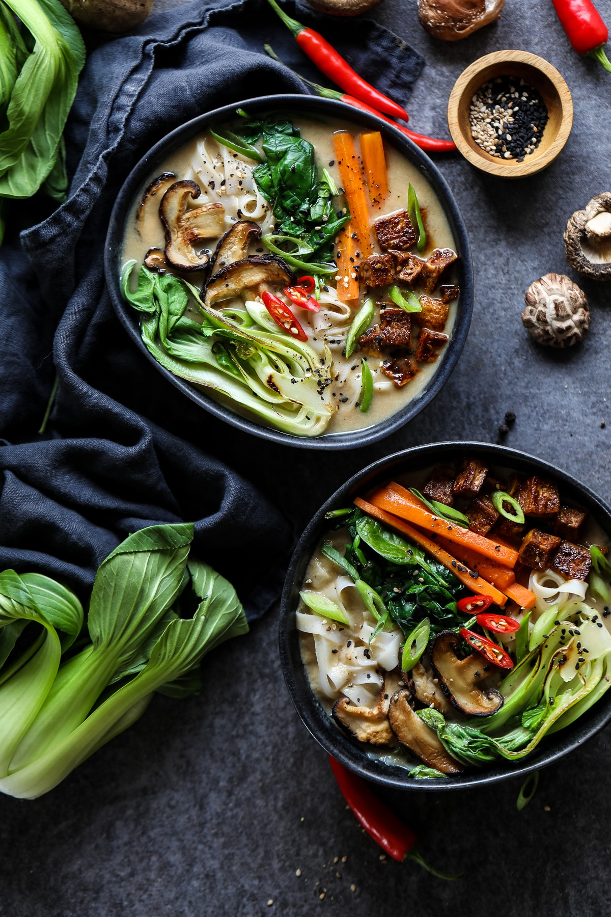 Two Vegan Ramen Bowls Surrounded by Ingredients.