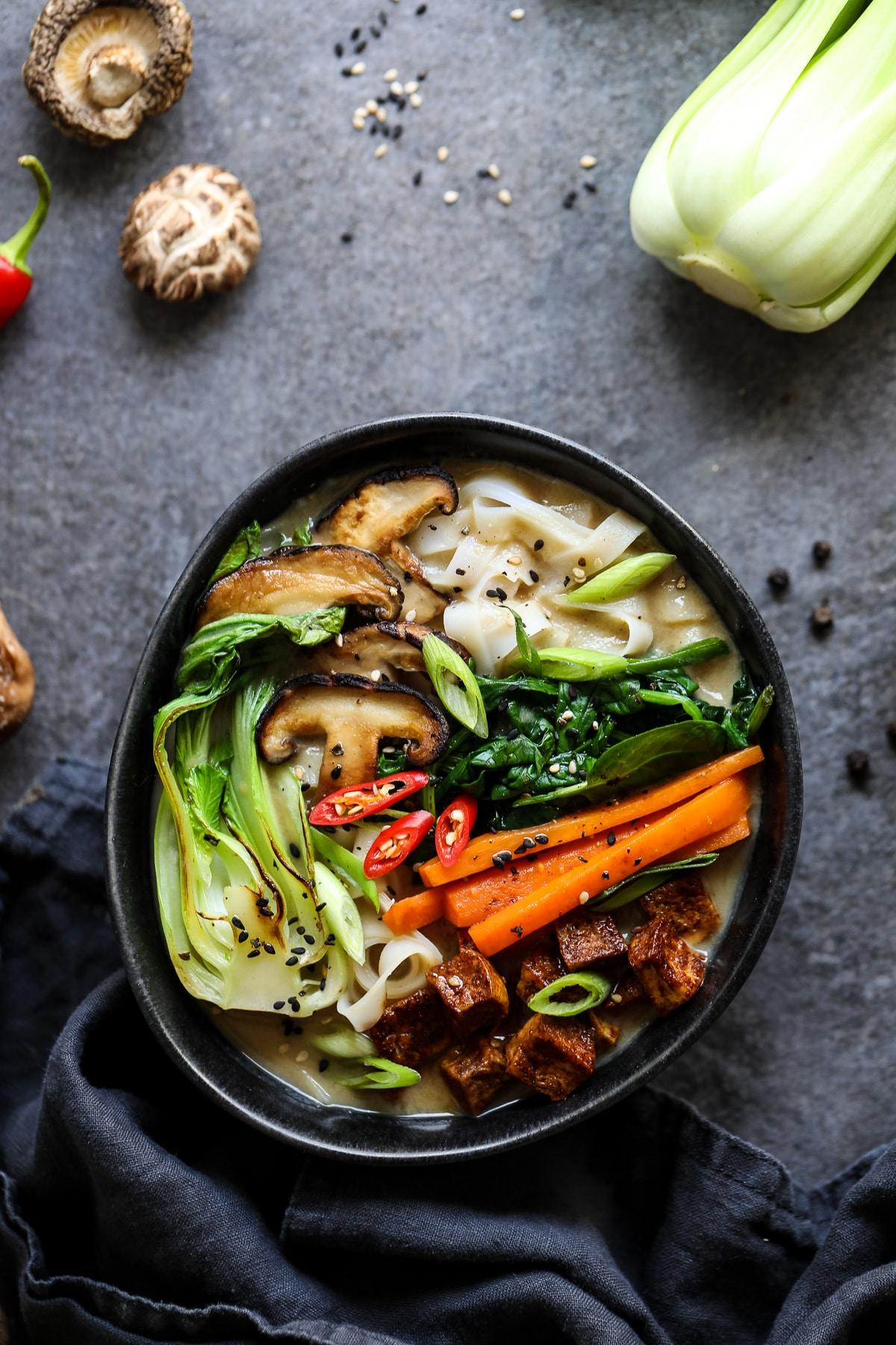 Vegetarian Ramen in a Black Bowl with Ingredient Props.