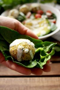 Crispy Baked Falafel with Hazelnuts and Creamy Lemon-Mint Sauce - Holding One in Hand