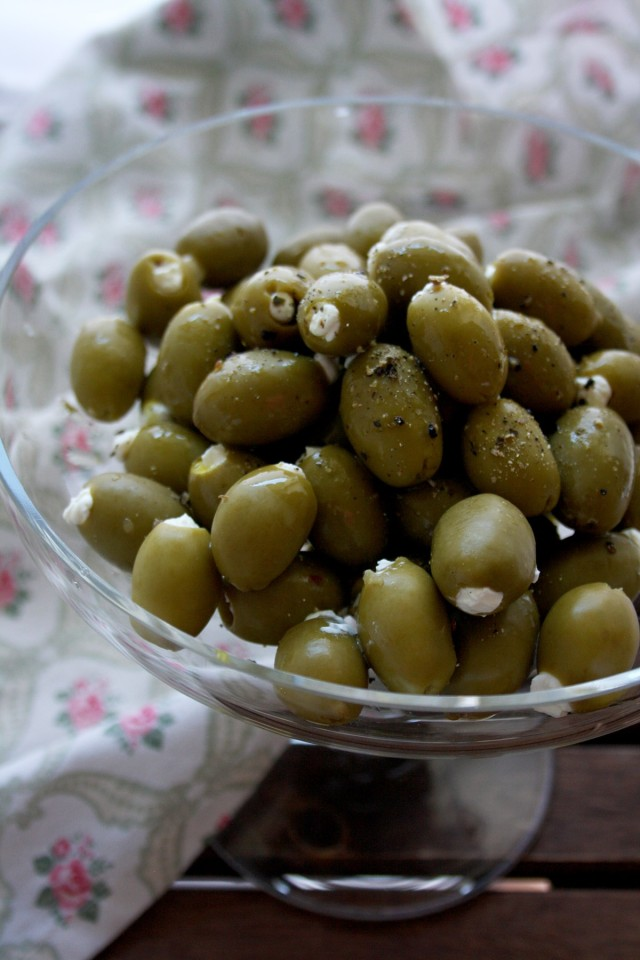 Cream Cheese Stuffed Olives in a Glass Bowl and a Cloth Near the Bowl