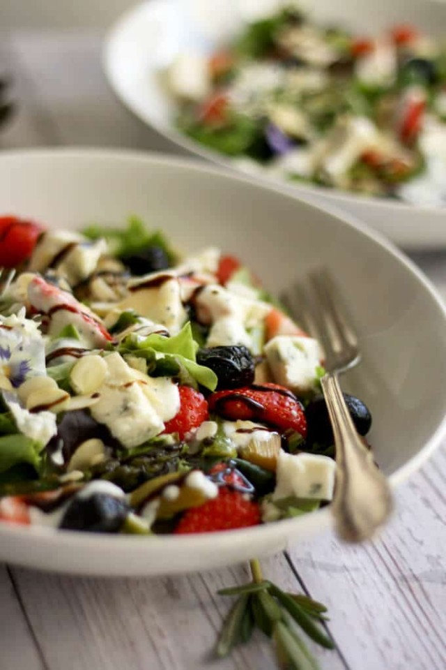 Strawberry Poppy Seed Salad with Asparagus and Rhubarb - Focus on the Serving with Another One Blurred in the Background