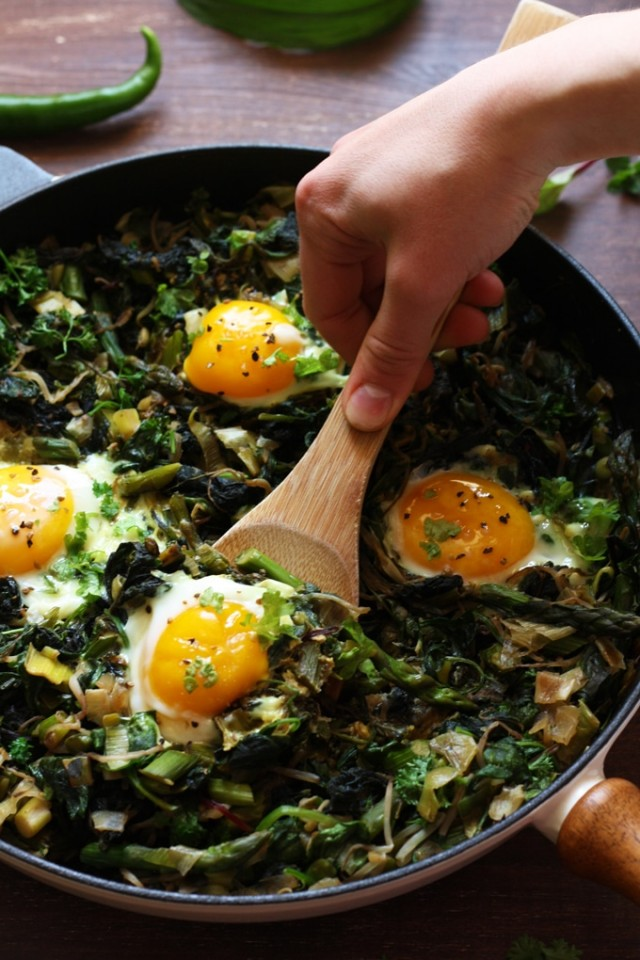 Green Shakshuka - Grabbing an Egg with a Wooden Spoon from the Pan