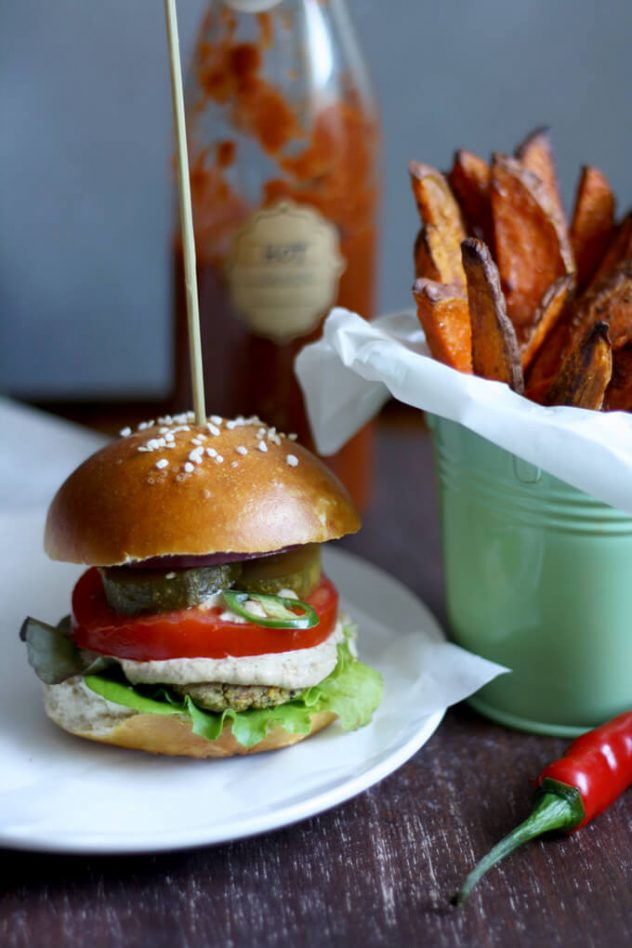 Juicy vegan falafel burger in a pretzel bun served with creamy tahini sauce and crispy and tender sweet potato fries. The best healthy falafel burger I've ever had!