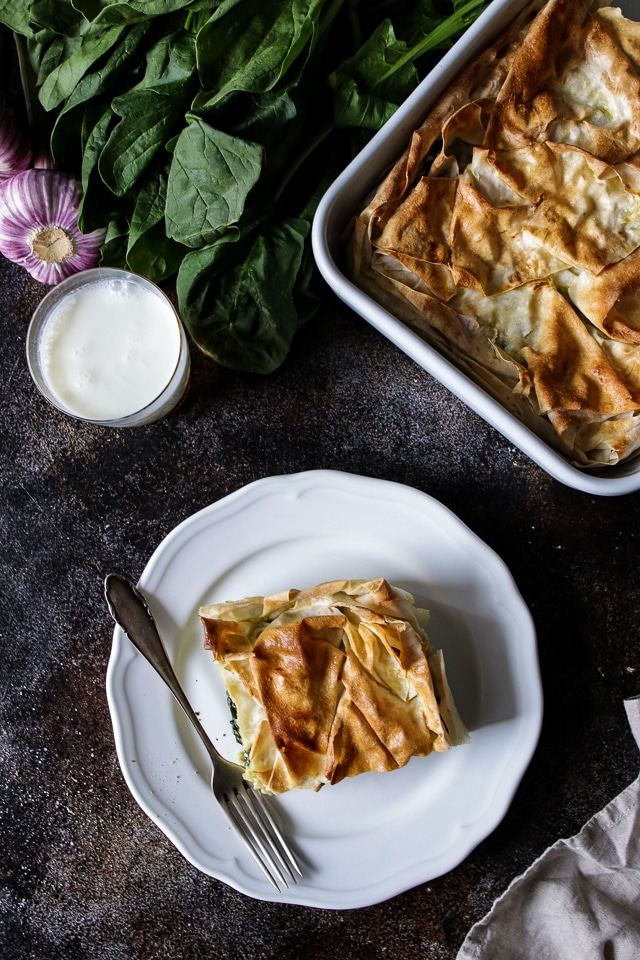 A Serving of Borek on a Plate Next to a Baking Dish and Raw Spinach