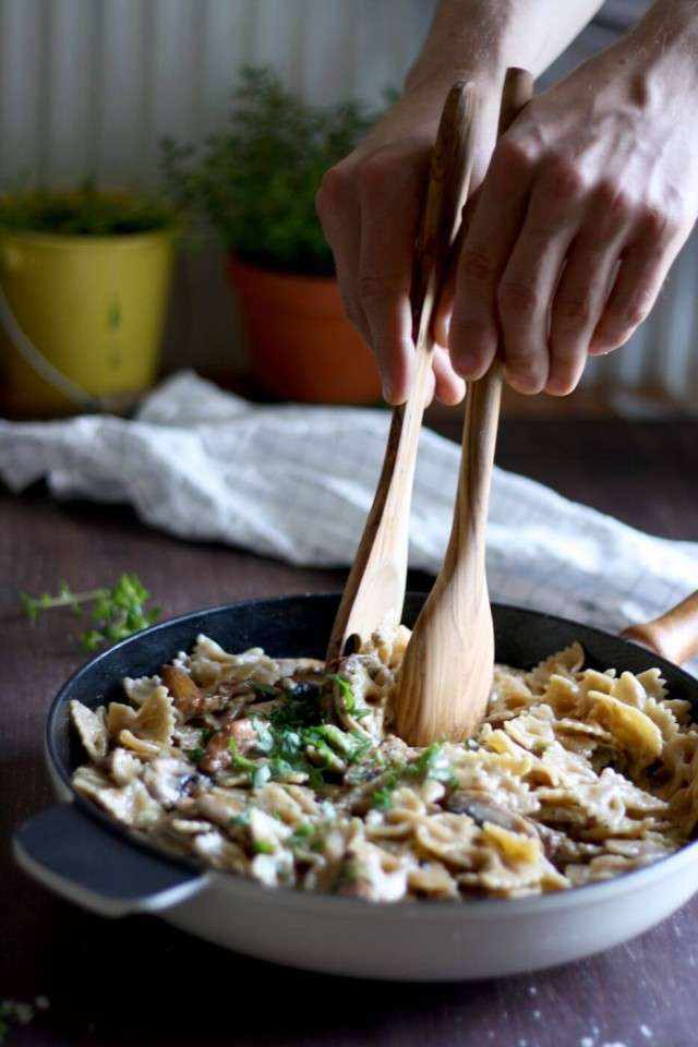 Rustic Creamy Mushroom Pasta with Hands in Action Ready to Serve