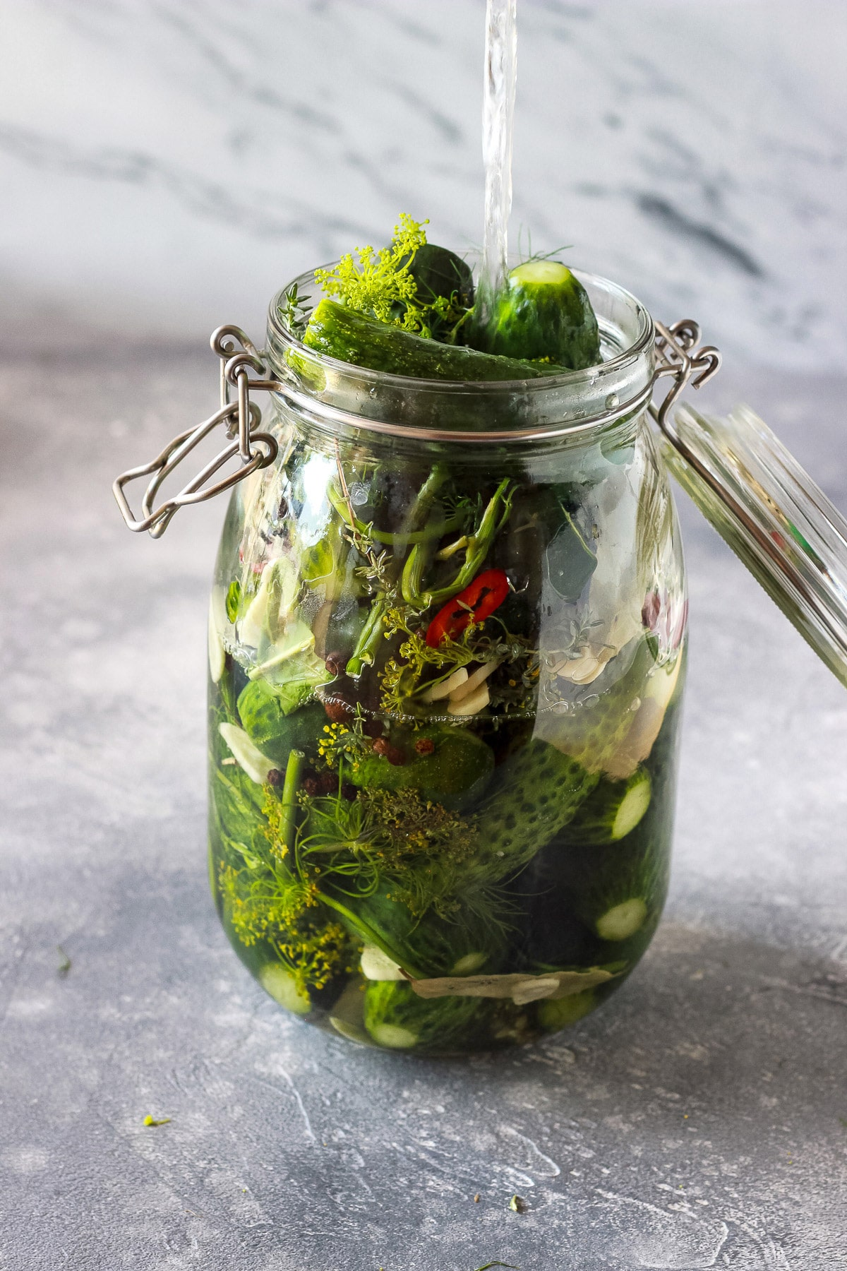 Pouring brine into a jar with cucumbers