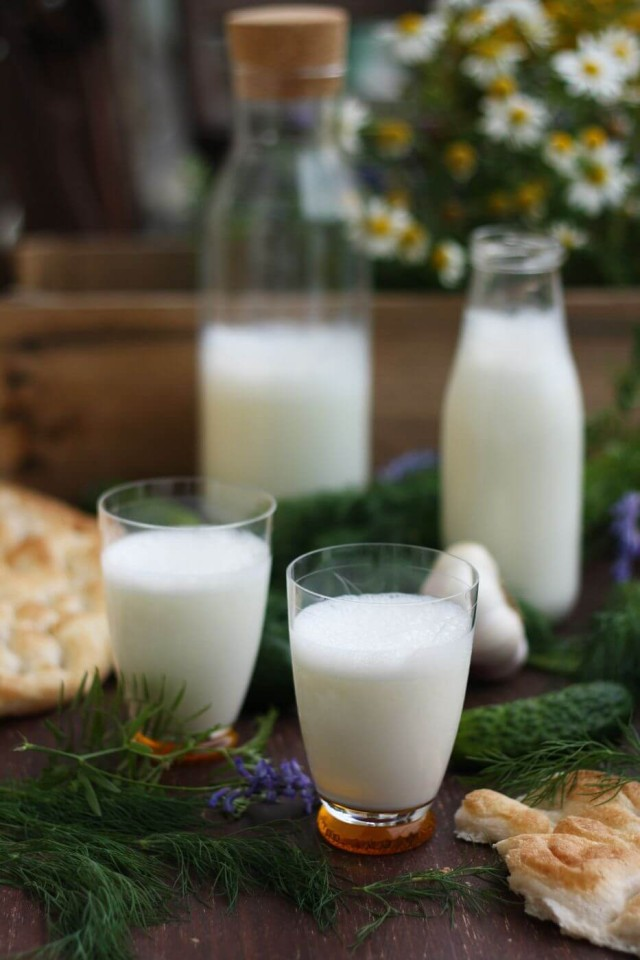 Turkish ayran served in glasses with pitchers on the background.