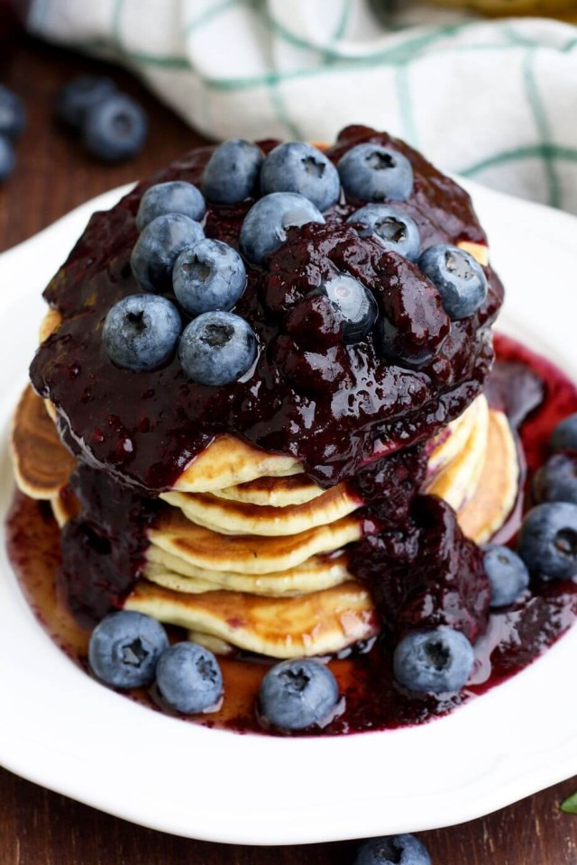 Blueberry Ricotta Pancakes Served in a White Plate Full of Blueberry Jam