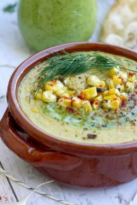 Vegan corn chowder soup with millet in a brown bowl.