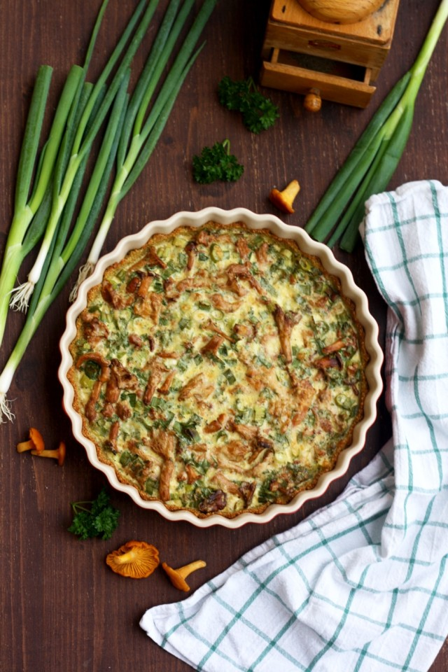 Mushroom quiche with quinoa pie crust in a baking dish with scallions