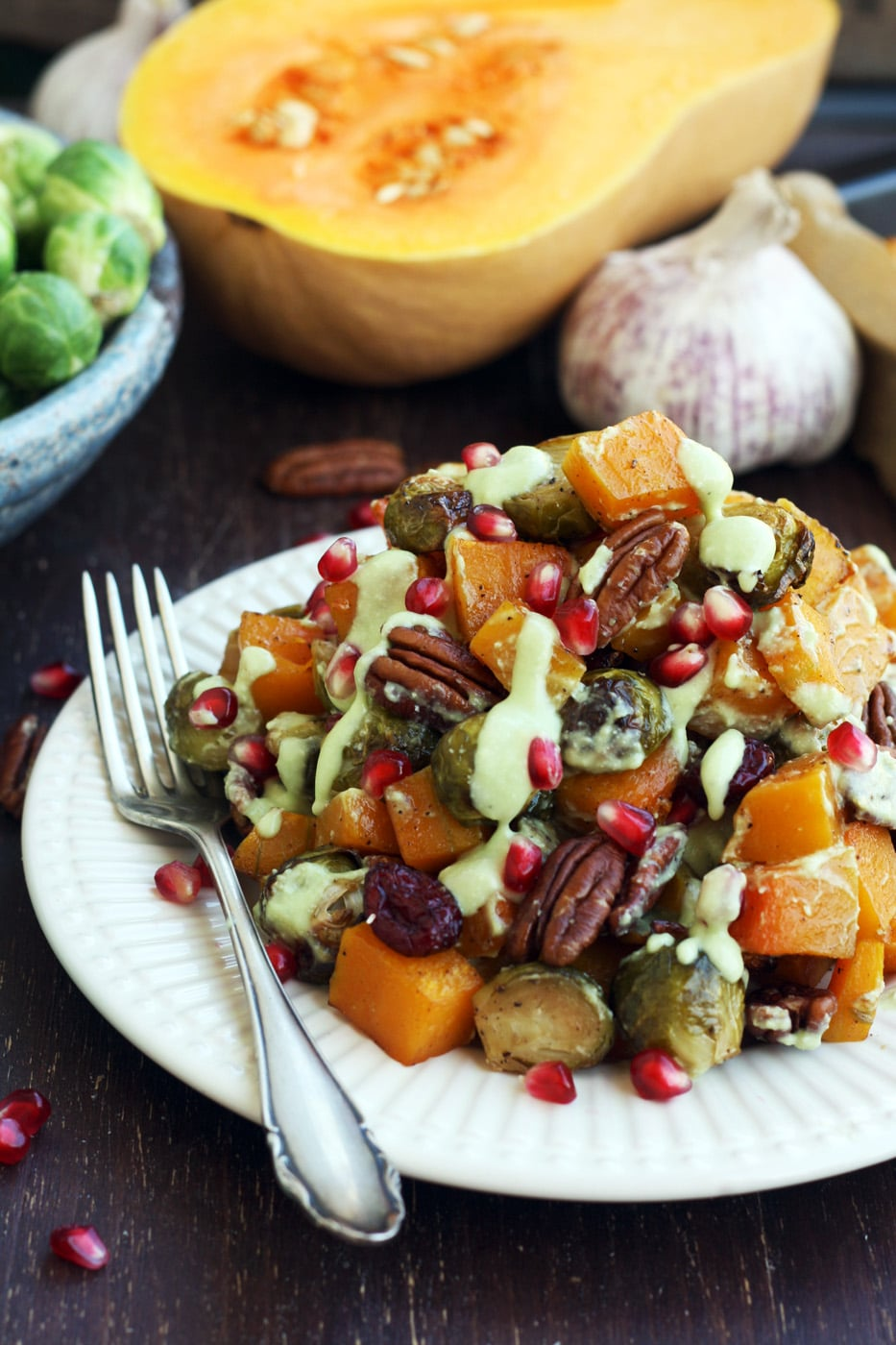 Roasted Brussels Sprouts with Butternut Squash Served on a Plate with Pomegranate Seeds on the Table