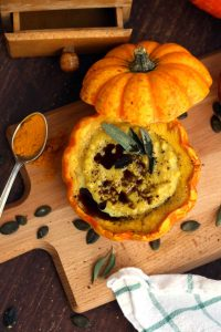 Easy Pumpkin Soup with Millet in Pumpkin Bowls - Served on the Wooden Board with a Spoon Full of Spice