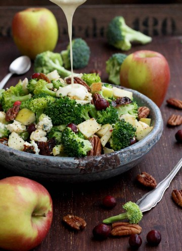 Healthy Broccoli Salad with Vegan Bacon, Apples, Blue Cheese and Pecans Pouring Dressing - in the Process of Pouring Sauce Over the Salad