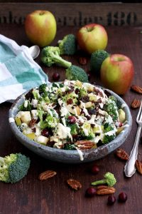 Healthy Broccoli Salad with Vegan Bacon, Apples, Blue Cheese and Pecans Pouring Dressing in a Grey Bowl with a Fork Next to It
