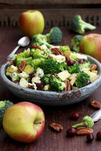 Healthy Broccoli Salad with Vegan Bacon, Apples, Blue Cheese and Pecans Pouring Dressing - Beautiful Composition Before the Dressing Being Poured Over