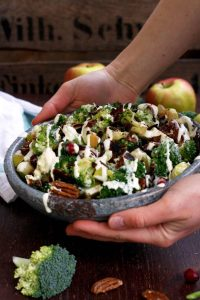 Healthy Broccoli Salad with Vegan Bacon, Apples, Blue Cheese and Pecans Pouring Dressing - Holding a Full Bowl in Hands