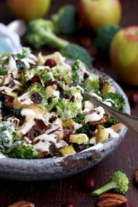 Healthy Broccoli Salad with Vegan Bacon, Apples, Blue Cheese and Pecans Pouring Dressing Closeup on the Dish with Apples Blurred in the Background