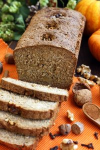 Healthy Pumpkin Bread with Walnuts - Cut into Pieces with Spices and Pumpkin in the Background