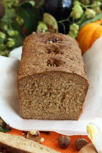 Healthy Pumpkin Bread with Walnuts on a White Paper Surrounded by Raw Ingredients