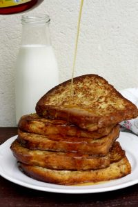 Healthier Brioche French Toast Pouring Syrup on Top with Milk in the Background