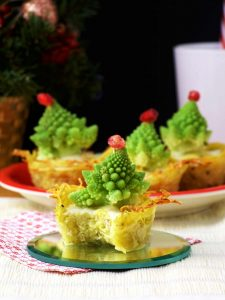 Christmas Tree Mini Quiches with One Quiche Bitten Once in the Foreground