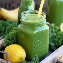 Delicious Kale Smoothie Closeup with Lemon and Greens Around