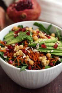 Healthy Sweet Potato Noodle Salad with Chickpeas and Rocket - Bowl Closeup with a Pomegranate in the Background
