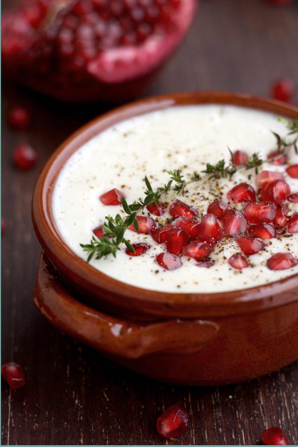 Vegan Cauliflower soup with coconut garnished with pomegranate seeds in a brown bowl.
