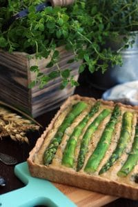 The Best Vegan Quiche Ever on a Wooden Tray with Wheat Next to It