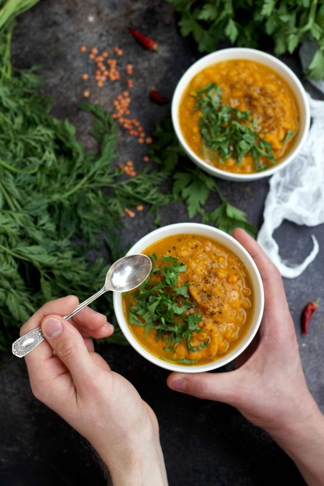 Vegan Roasted Carrot Soup with Lentils - Holding a Bowl with a Spoon Ready to Eat