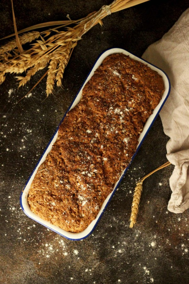 Healthy Wholemeal Bread in a Loaf Pan Flatlay with Flour and Wheat on the Table