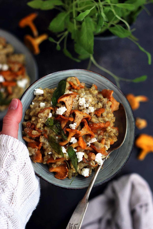 Easy Barley Risotto with Mushroom and Goat Cheese Hand Holding a Bowl above the Table Full of Raw Chanterelles