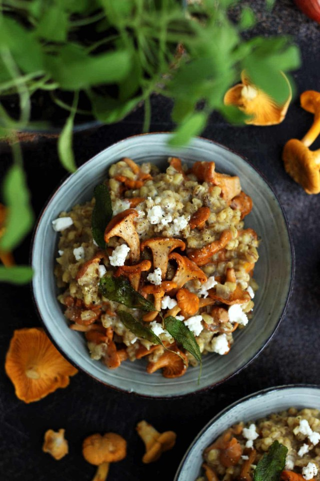 Easy Barley Risotto with Mushroom and Goat Cheese in a Bowl Flatlay with Greensin the Foreground and Raw Chanterelles Lying Around