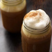 Healthy Vegan Pumpkin Spice Latte in a Mason Jar Topped with Cashew Whipped Milk Being Sprinkled with Cinnamon