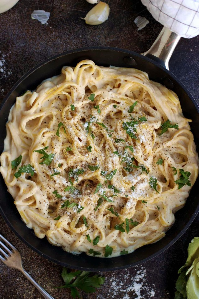 The Creamiest Vegan Fettuccine Alfredo - in a Skillet with Fork and Glove of Garlic Laying Around