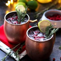 Cranberry Moscow Mule - Served in Copper Mugs with Lights in the Background