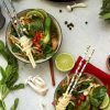 Easy Vegan Pho (Vietnamese Noodle Soup) Overhead with Two Bowls and Plenty of Ingredients on the Table