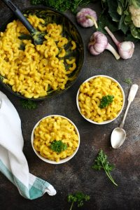 #ad Silky Vegan Mac and Cheese Overhead Shot on Two Bowls and a Pan with Garlic and Herbs Around
