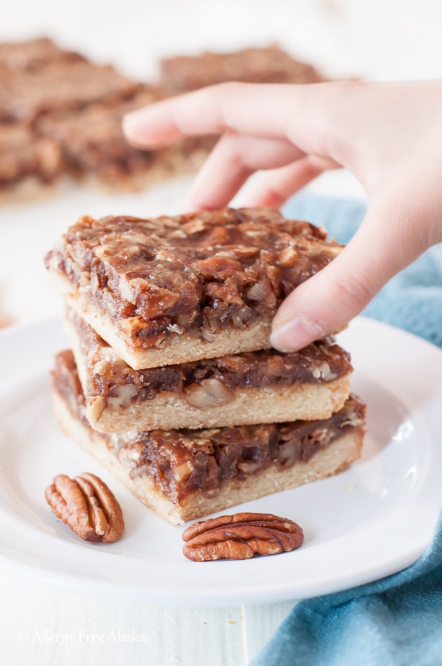 Hand Taking the Upper Piece from The Stalk of Vegan Paleo Pecan Pie Bars.