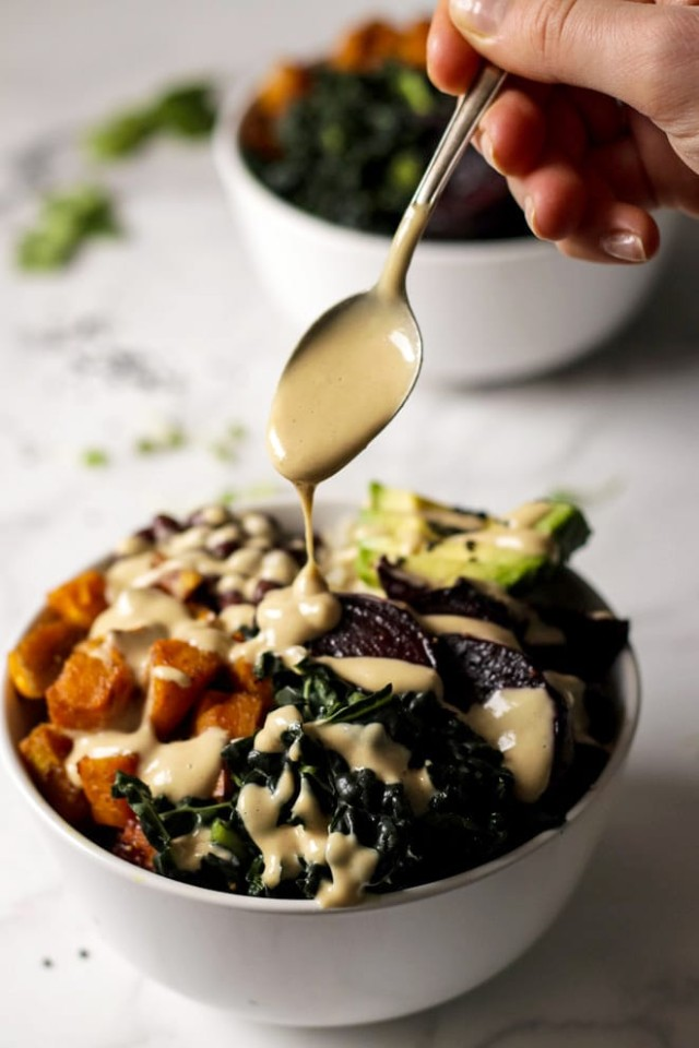 Tahini Dressing Being Poured Over a Bowl of Roasted Vegetables
